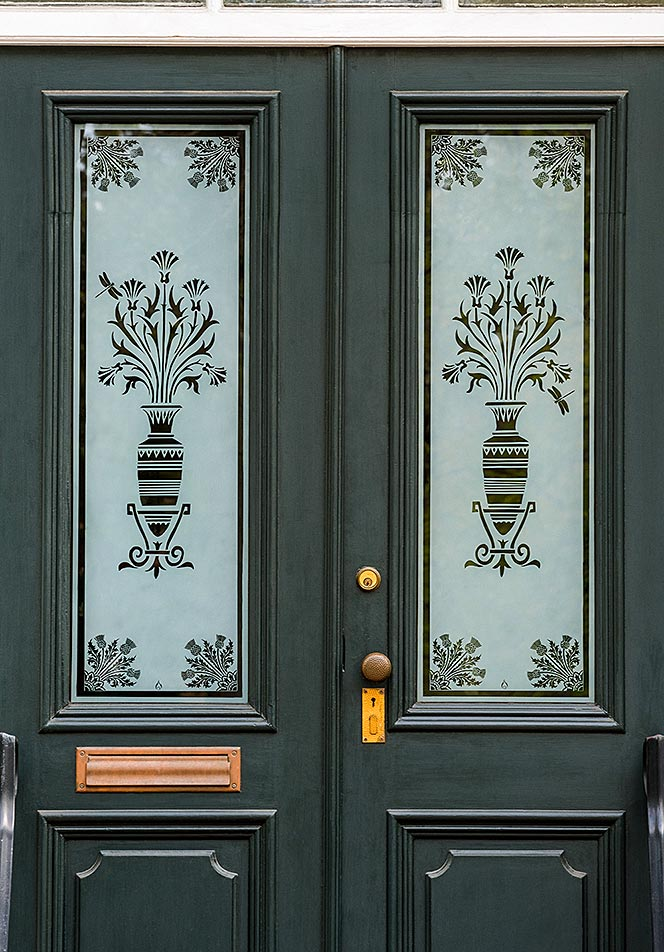 A double door entry way on a historic home with art-deco style etched flower vases